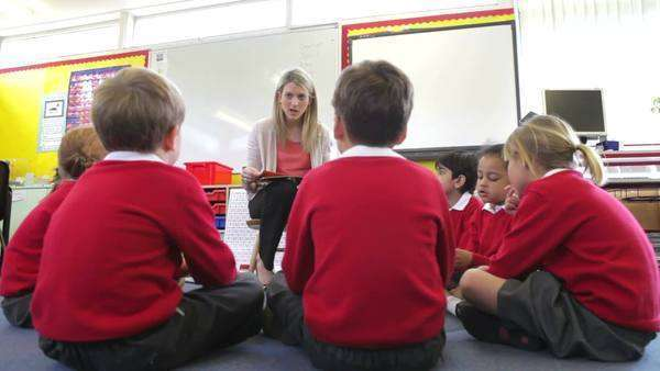Pupils sit in circle on floor as teacher reads to them.. Royalty-free stock video