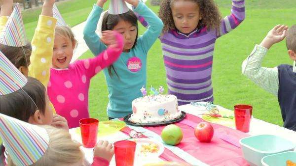 Camera follows group of children as they sit around table and enjoy food at birthday party. Royalty-free stock video