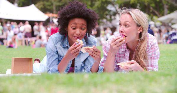 Two friends lying on the grass and eating cakes at an event Royalty-free stock video