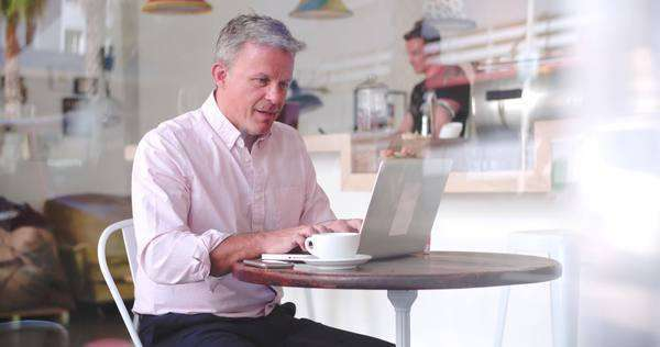 Businessman at a table in a cafe using laptop Royalty-free stock video