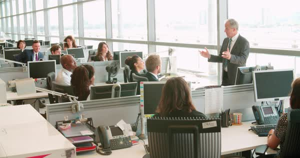 Senior male manager addressing workers in open plan office Royalty-free stock video