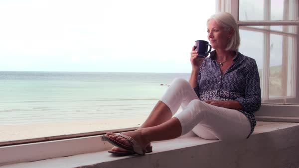 Woman sits at window and looking at beach view Royalty-free stock video