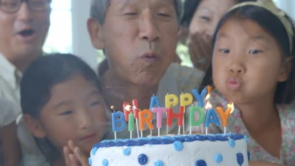 Grandfather blows out candles on birthday cake Royalty-free stock video