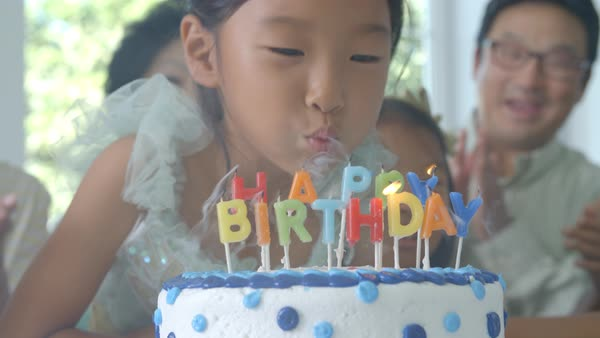 Slow motion shot as girl blows out candles on birthday cake Royalty-free stock video