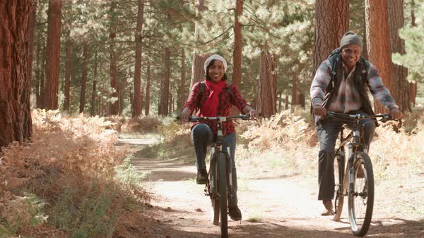Senior couple cycle past camera on a forest trail Royalty-free stock video