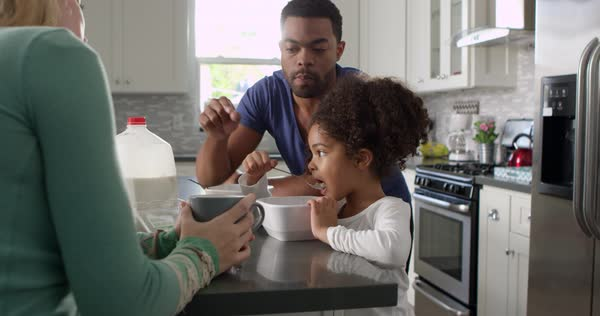 Couple and daughter eating breakfast in kitchen Royalty-free stock video