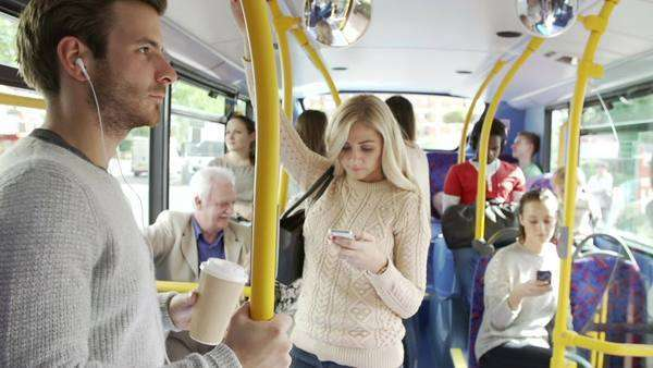 Interior of crowded bus with passengers listening to music and using mobile phone. Royalty-free stock video