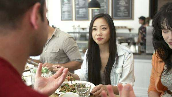 Group of friends sitting at table in café eating and chatting. Royalty-free stock video
