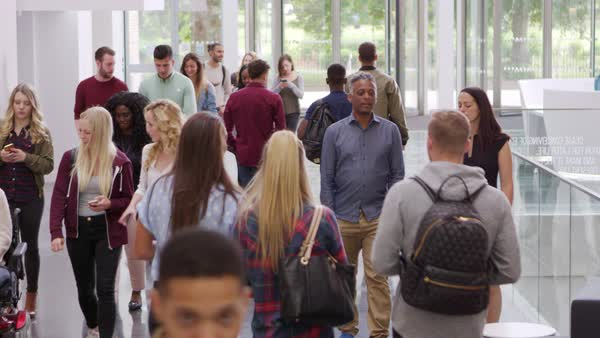 Students and teachers walk in foyer of a modern university, shot on R3D Royalty-free stock video