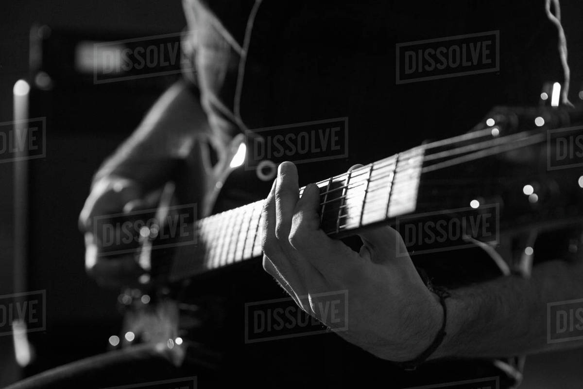 Close Up Of Man Playing Electric Guitar Shot In Monochrome Stock