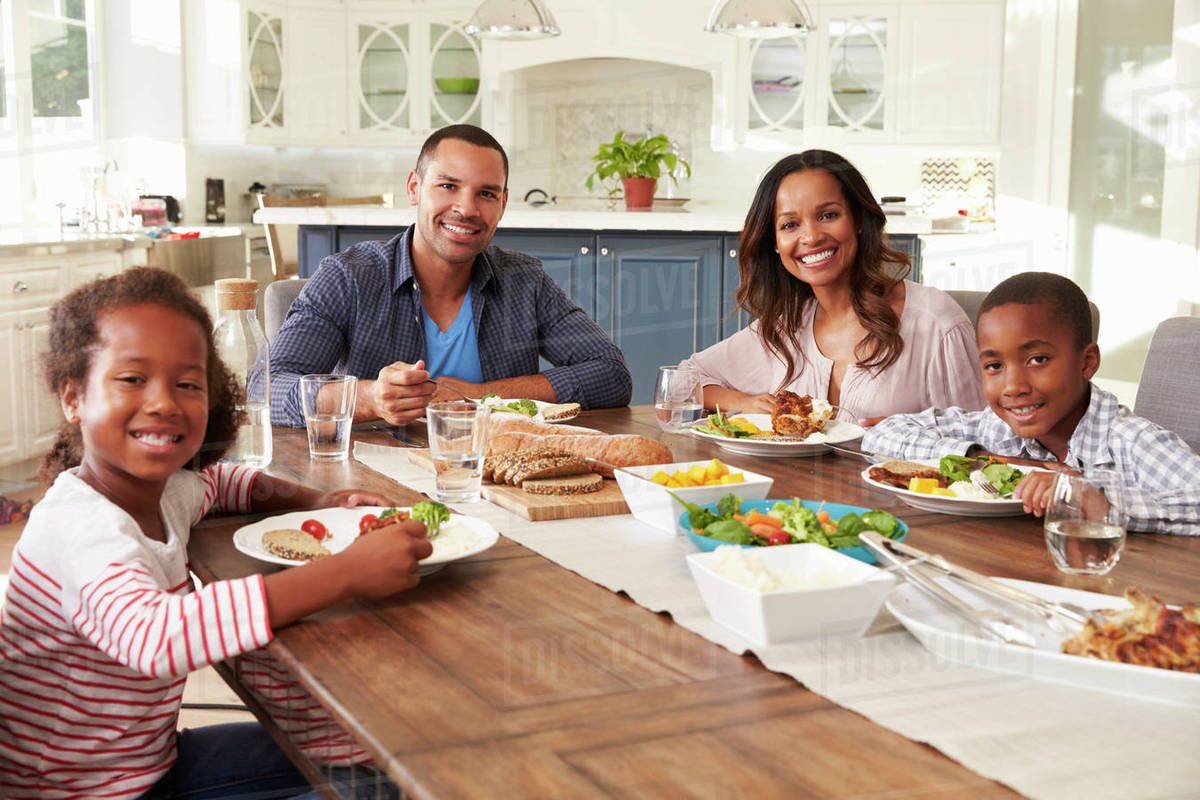 Super Parents And Children Eating At Kitchen Table Look To Camera Stock Photo Download Free Architecture Designs Embacsunscenecom
