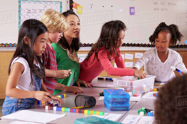 Elementary school teacher uses block play in class with kids Royalty-free stock photo