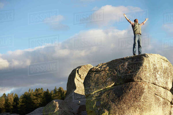 Man standing on rocky outcrop with arms raised Royalty-free stock photo