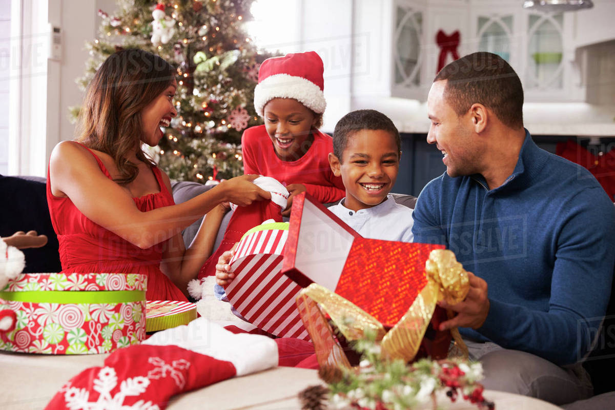Family opening Christmas presents at home together - Stock ...