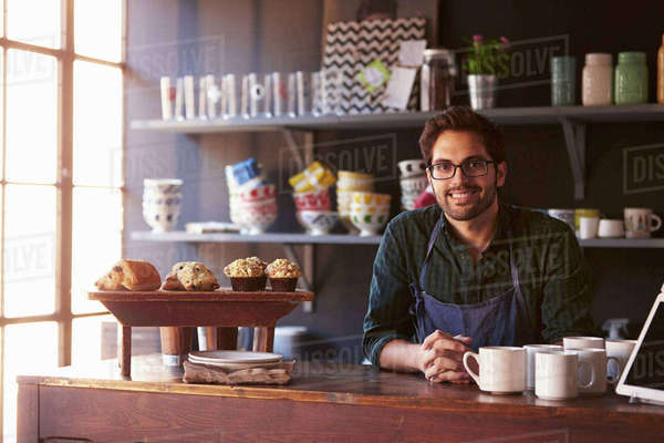 Portrait Of Male Coffee Shop Owner Standing Behind Counter Royalty-free stock photo