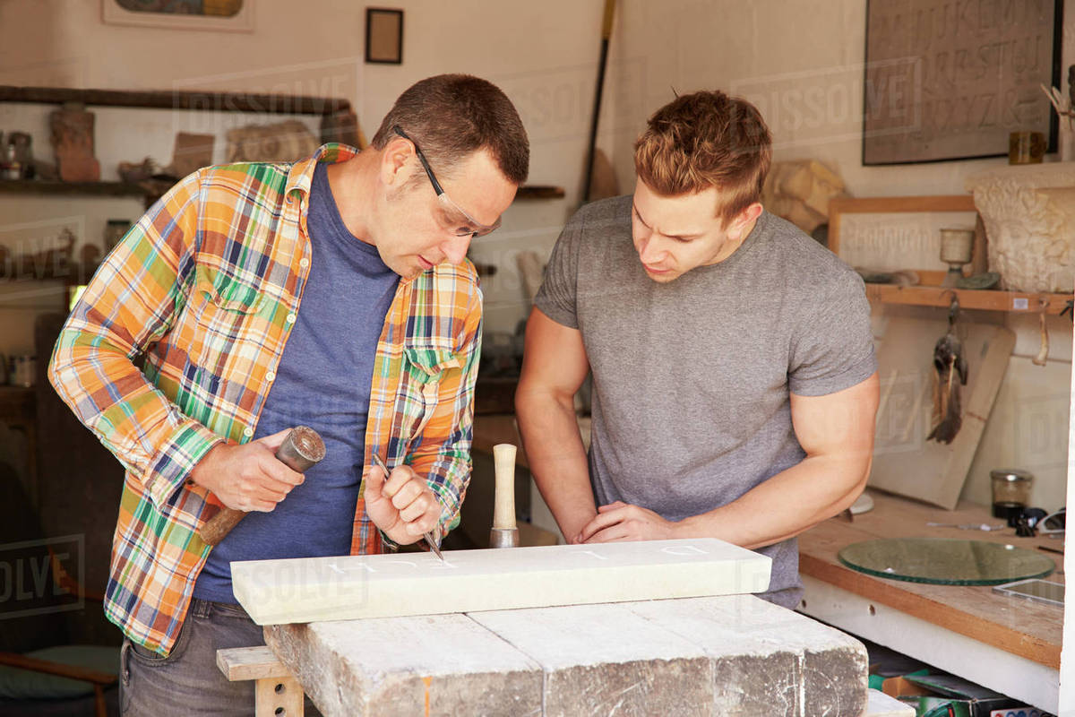 Stone Mason With Apprentice At Work On Carving In Studio stock photo