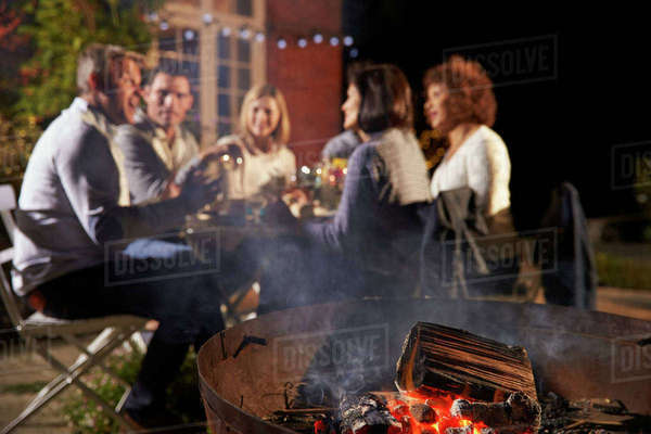 Mature Friends Enjoying Outdoor Evening Meal Around Firepit Royalty-free stock photo