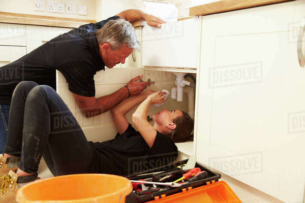 Plumber training female apprentice to fit a kitchen sink Royalty-free stock photo