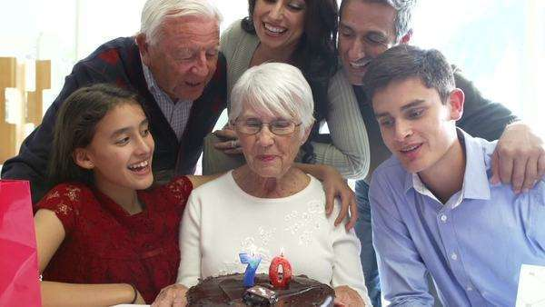 Family singing happy birthday to grandmother before she blows out candles in slow motion. Royalty-free stock video