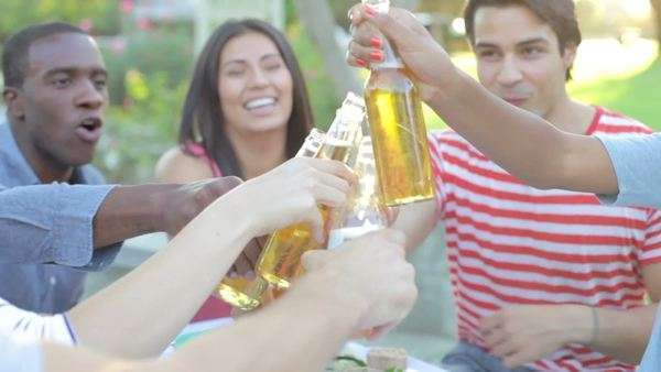Group of friends sitting at table having meal together - they make a toast with bottles of beer. Royalty-free stock video