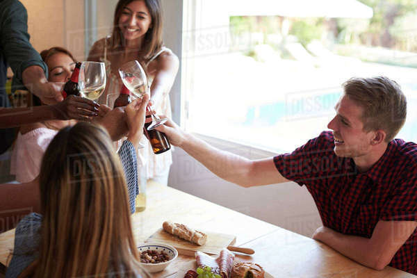 Five friends make a toast at a dinner party in the kitchen Royalty-free stock photo