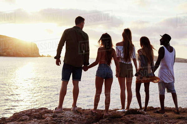 Rear View Of Friends Standing On Cliff Watching Sunset Royalty-free stock photo