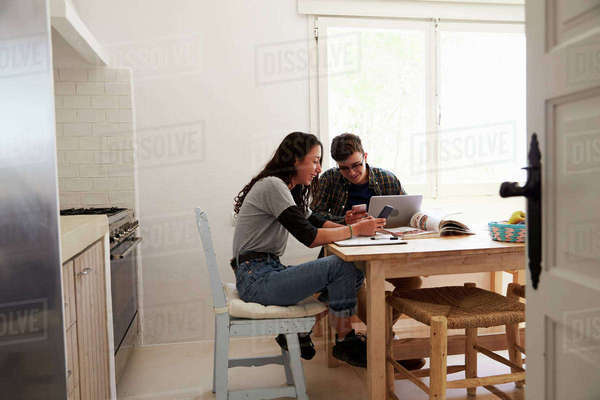 Two teenagers with laptop using smartphones at kitchen table Royalty-free stock photo