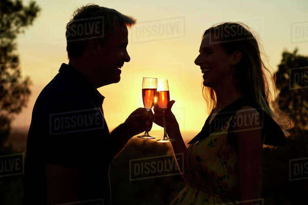 Romantic couple making a toast outdoors at sunset, waist up Royalty-free stock photo