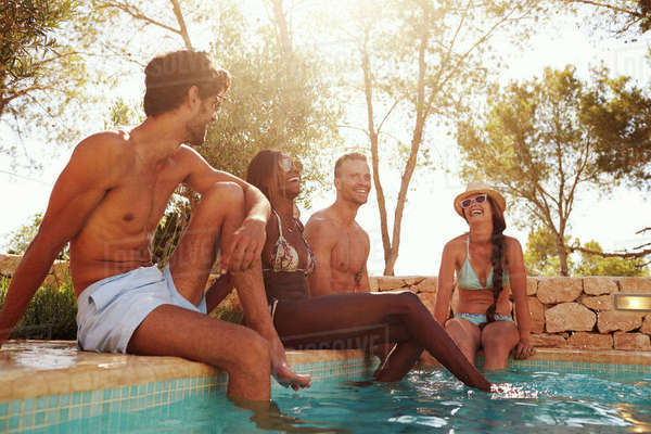 Group Of Friends On Vacation Relaxing Next To Outdoor Pool Royalty-free stock photo