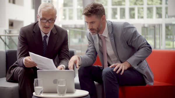 Two businessmen discuss document in lobby of modern office Royalty-free stock video