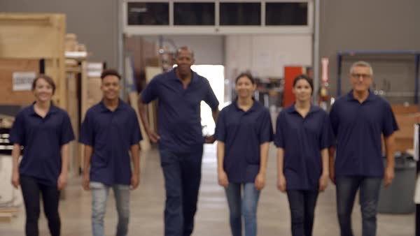Engineers and apprentices walk towards camera in factory Royalty-free stock video