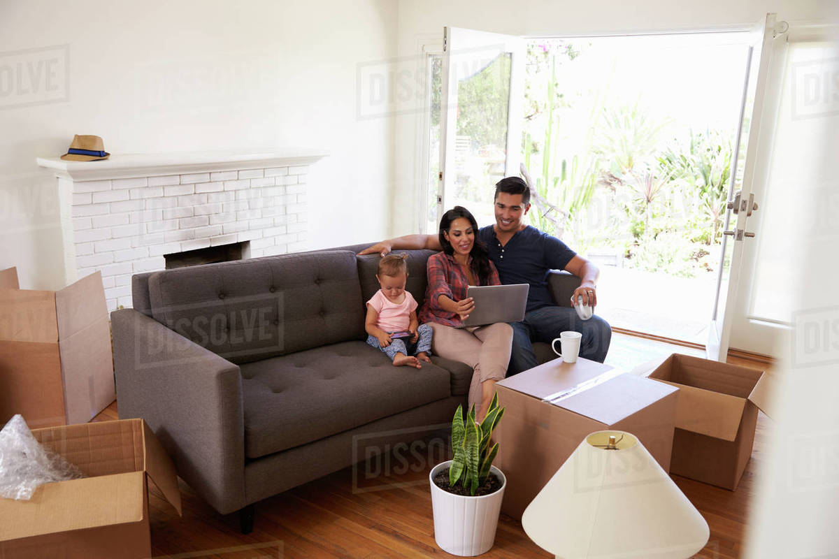 Family Take A Break On Sofa Using Laptop Moving Day