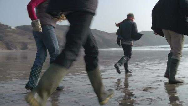 Family running along beach away from camera in slow motion. Royalty-free stock video