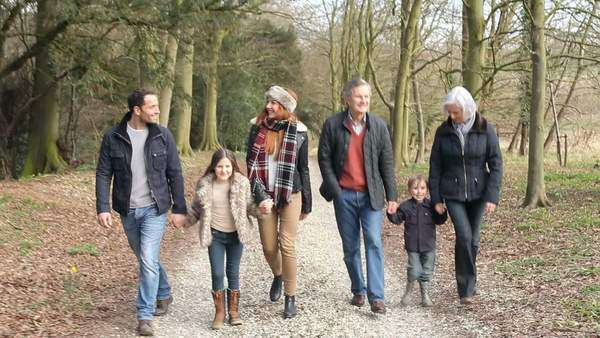 Multi generation family in countryside walking towards camera along path as children run ahead. Royalty-free stock video