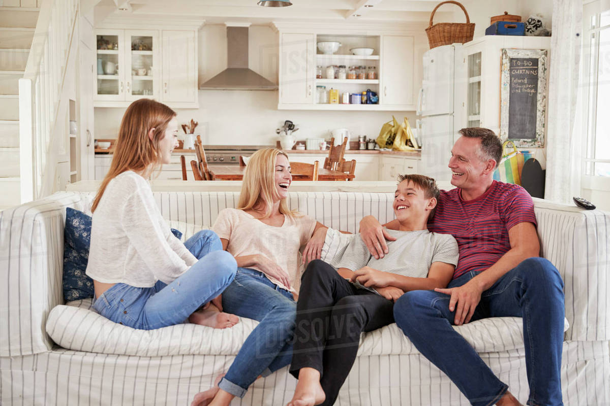 family with teenage children sitting on sofa watching tv. Black Bedroom Furniture Sets. Home Design Ideas
