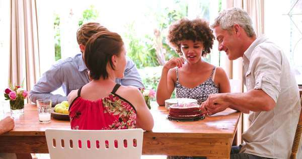 Man cutting birthday cake and sharing with friends who are helping