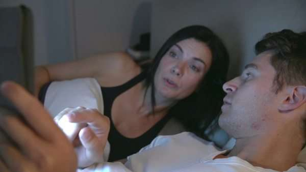 Couple lying in bed looking at digital tablet together. Royalty-free stock video