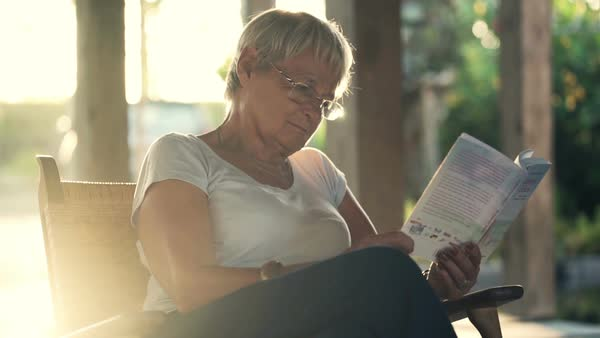 Woman reading book sitting on patio in garden Royalty-free stock video