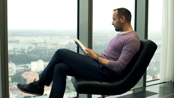 Man reading book sitting on chair by window at home Royalty-free stock video