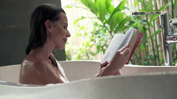 Pretty, young woman reading book during bath in open bathroom Royalty-free stock video