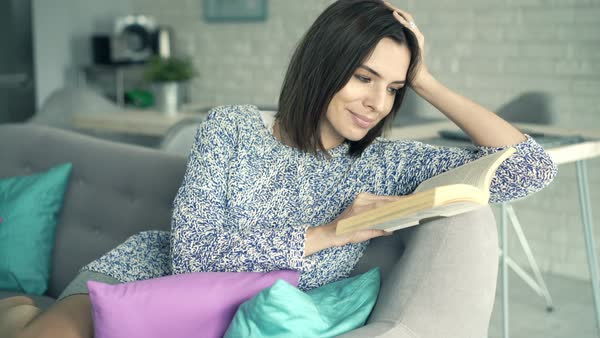 Young woman reading book on sofa at home Royalty-free stock video