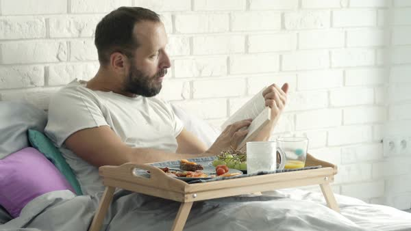 Man reading book during breakfast lying on bed at home Royalty-free stock video