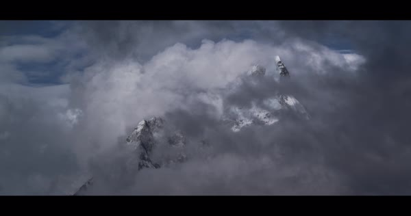 Locked off shot of a snowy mountain peak surrounded by heavy clouds Rights-managed stock video
