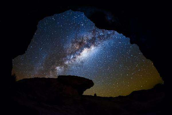 Dolly shot showing the night sky full of stars and the daylight through a natural arch Rights-managed stock video
