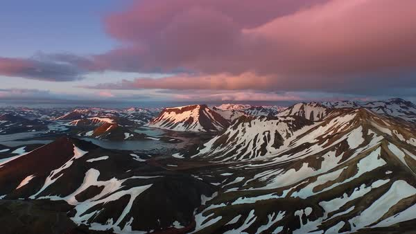 Aerial shot of clouds moving over snowcapped mountains at sunset Royalty-free stock video