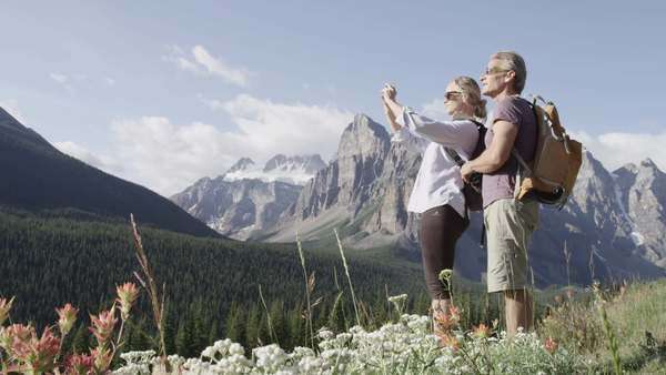 Wide shot of couple taking pictures in the mountains Royalty-free stock video