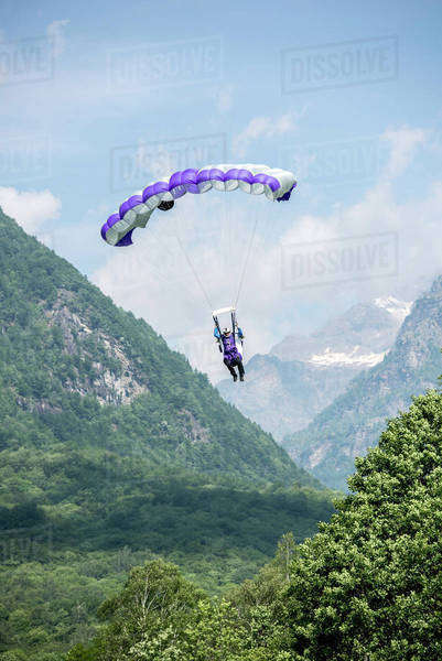Wingsuit flyer gliding at a mountain in Ticino canton, Switzerland Royalty-free stock photo