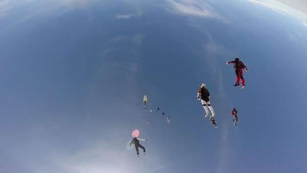 Sky divers plunge from plane, fall towards clouds and fields Royalty-free stock video