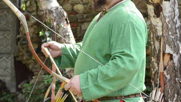 Middle Ages archer wearing green shirt shoot deadly arrows with his bow Royalty-free stock video