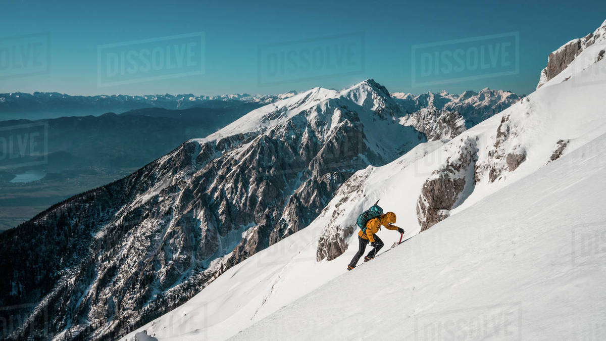 A man climbs up in the winter steep snow slope to reach the summit of Vrtača, Karavanke, Slovenia Royalty-free stock photo